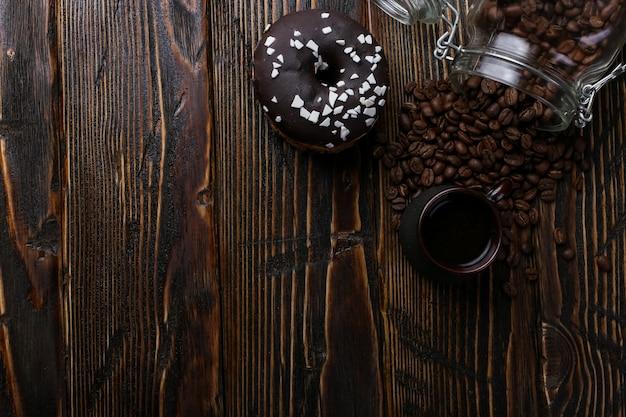Donut com cobertura preta e pó de chocolate e uma autêntica xícara de café forte. uma lata de grãos de café e grãos derramados.