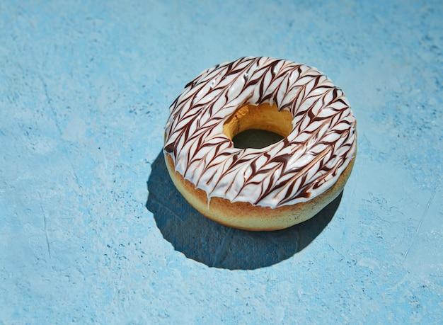 Donut com glacê branco e granulado sobre fundo azul.