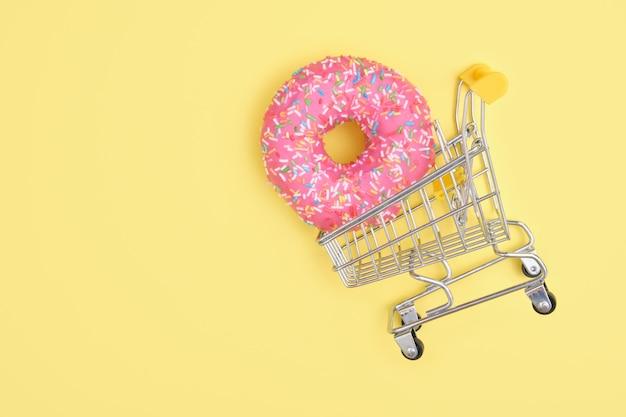 Donut com granulado e glacê rosa em um carrinho de compras na superfície amarela, vista superior, copie o espaço