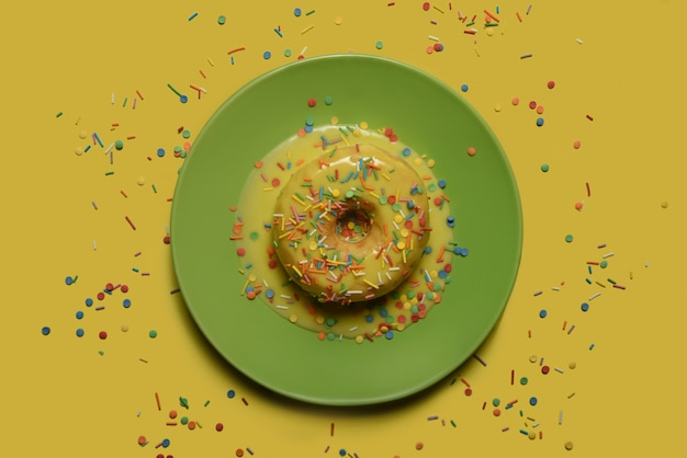Donut com vidros amarelos e pó multi-colorido em um prato verde