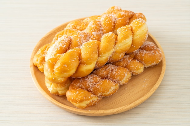 Donut de açúcar em forma de espiral em placa de madeira