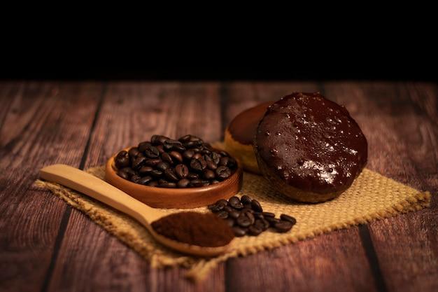 Donut de café com grãos de café orgânicos e pó de café na colher de pau na mesa de madeira