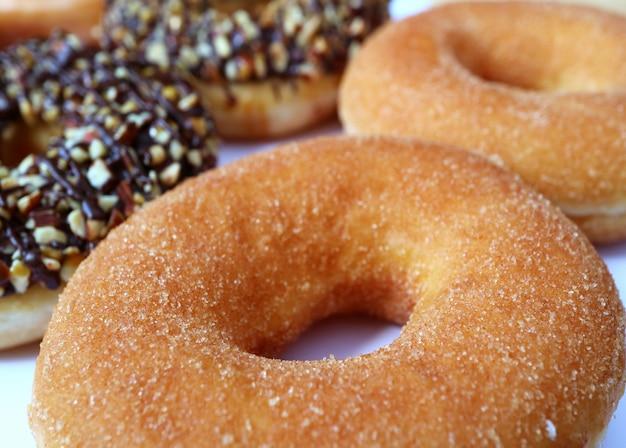 Donut de canela de dar água na boca com donuts de chocolate de amêndoa turva em fundo