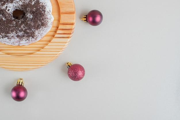 Donut de chocolate com bolas de natal.