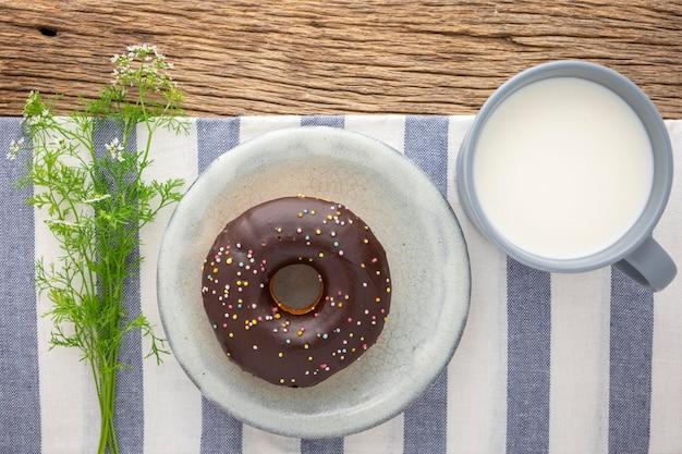 Donut de chocolate com granulado em prato de cerâmica ao lado de um copo de leite e flores no guardanapo e fundo de textura rústica de madeira natural, refeição fácil para o intervalo, vista de cima