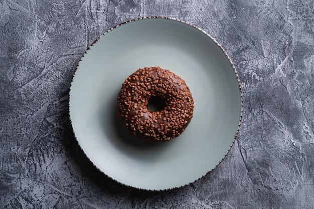 Donut de chocolate com granulado na chapa cinza