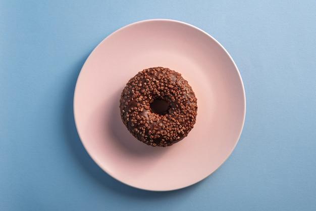 Donut de chocolate com granulado no prato rosa