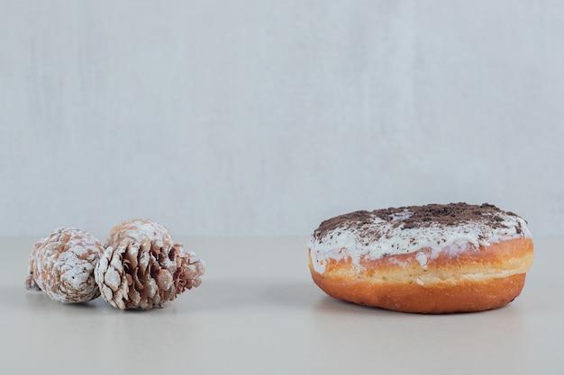 Donut de chocolate com pinhas de natal.