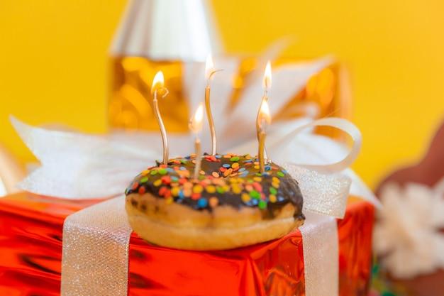 Donut de chocolate doce e velas acesas em um fundo de bokeh festivo. conceito de feliz aniversário.
