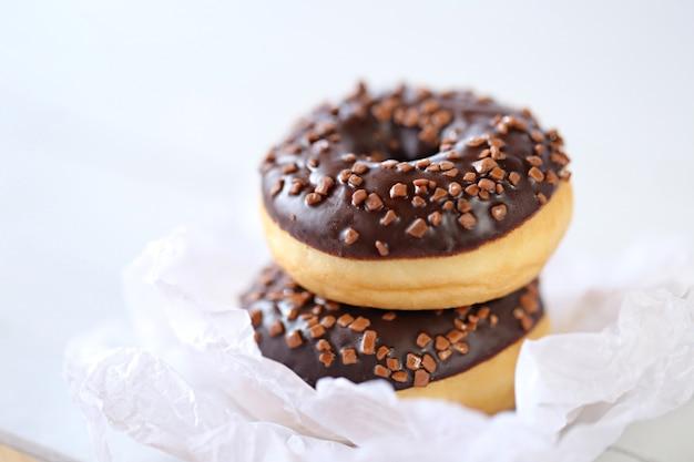 Donut de chocolate em papel amassado branco sobre uma luz embaçada