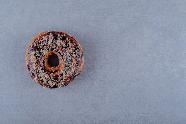 Donut de chocolate fresco na superfície cinza. vista do topo