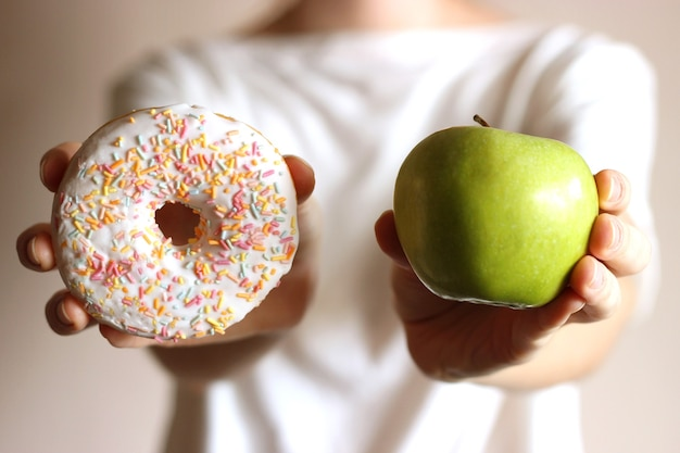 Donut e maçã em mãos femininas escolha de alimentos saudáveis e não saudáveis