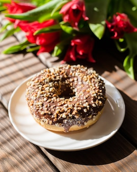 Donut em chapa branca com tulipas em uma superfície de madeira marrom. café da manhã no verão