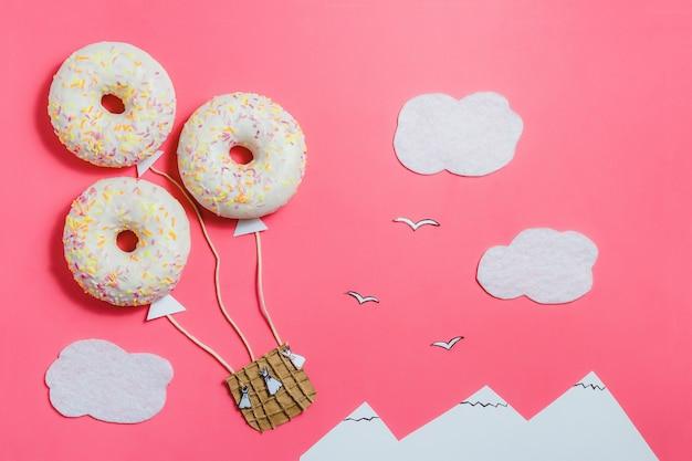 Donut em forma de aerostat no céu rosa com nuvens