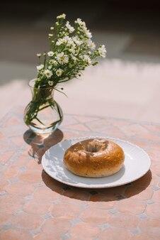 Donut em prato branco no fundo da mesa sob luz natural do sol