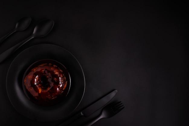 Donut em uma placa preta com talheres preto sobre um fundo preto, vista superior