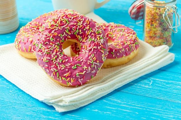 Donut em uma toalha de cozinha e na mesa de madeira azul. foto de doces.