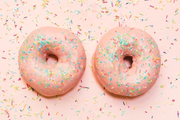 Donut fosco com granulado colorido sobre superfície rosa