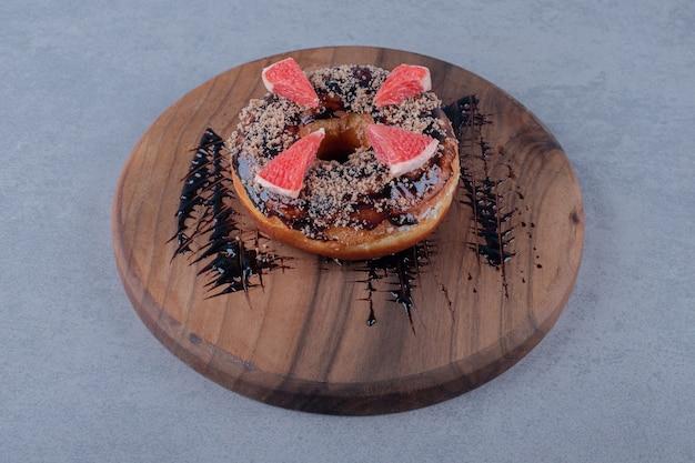 Donut fresco com fatias de toranja na placa de madeira