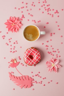 Donut gelado com decoração listrada e xícara de café expresso em um fundo rosa pastel