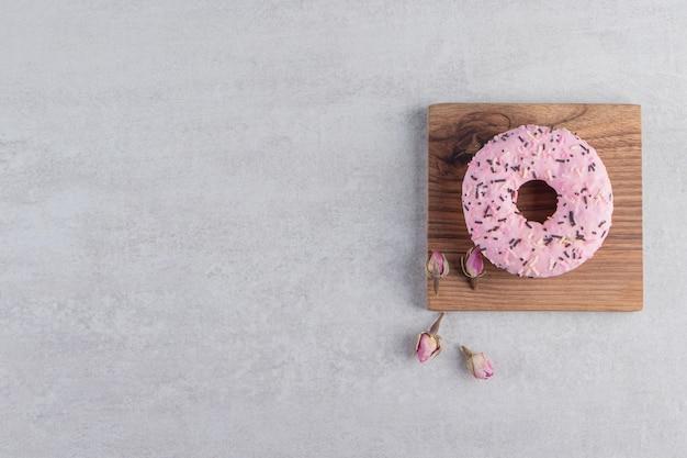 Donut rosa doce decorado com granulado na placa de madeira.