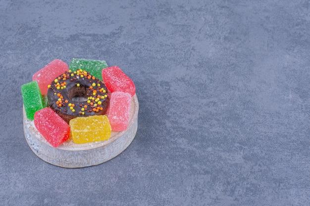 Donut saboroso com balas de geleia de frutas em uma superfície cinza