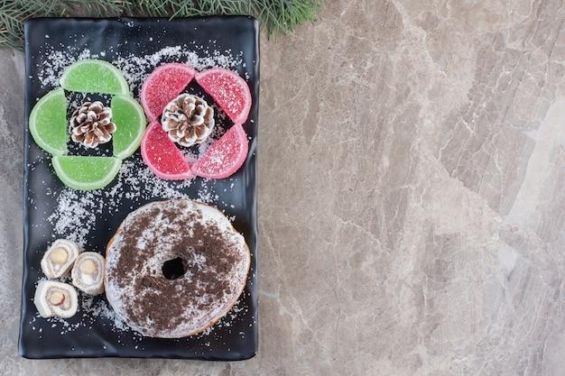 Donut vitrificado, delícias turcas e marmeladas em bandeja sobre mármore.