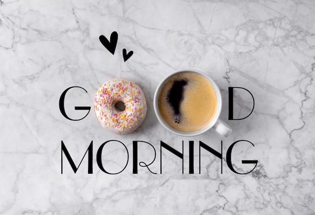Donut, xícara de café e corações. bom dia saudação escrita em mármore cinza