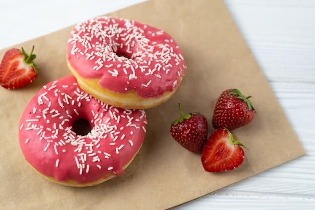 Donuts caseiros recém-assados com cobertura de morango rosa na mesa branca