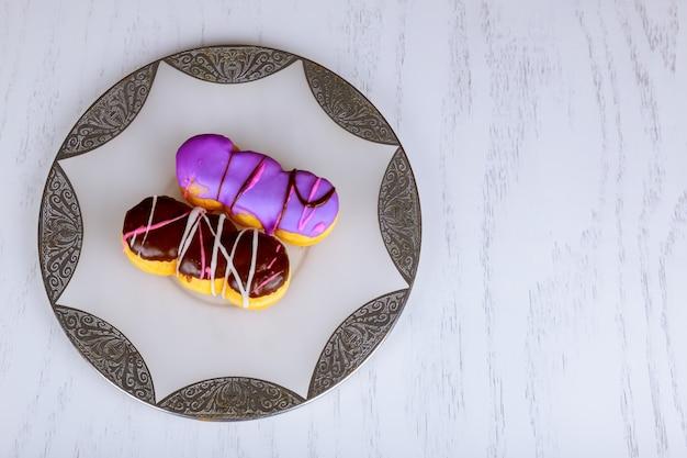 Donuts coloridos caseiros com cobertura de chocolate e glacê em fundo de madeira