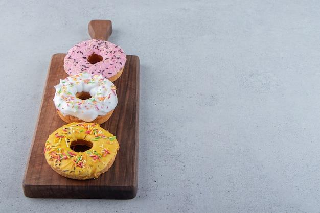 Donuts coloridos decorados com granulado na placa de madeira. foto de alta qualidade