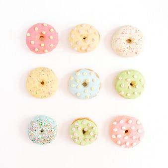 Donuts coloridos sobre fundo branco. camada plana, vista superior