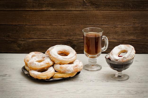 Donuts com açúcar de confeiteiro, uma caneca de chá e geléia de groselha em um de madeira