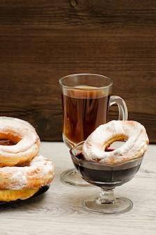 Donuts com açúcar de confeiteiro, uma caneca de chá e geléia de groselha em uma superfície de madeira