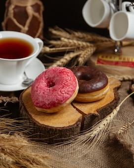 Donuts com creme vermelho e chocolate e uma xícara de chá.