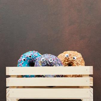 Donuts com olhos em caixa de madeira