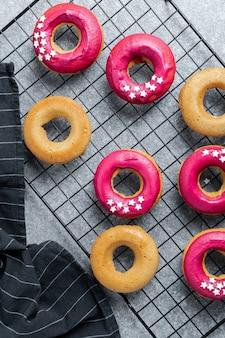 Donuts cozidos frescos com glacê rosa brilhante no rack de arrefecimento
