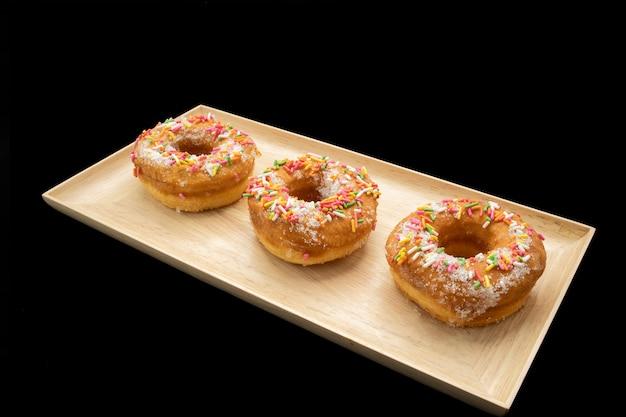 Donuts de açúcar tradicionais com granulado multicolor em uma placa de madeira.
