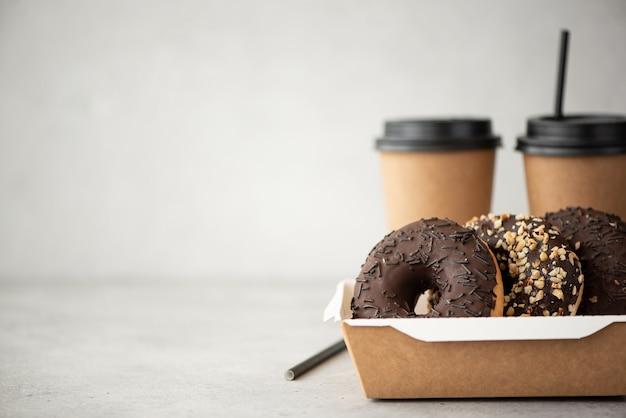 Donuts de chocolate com cobertura em uma caixa artesanal e café preto em xícaras em uma mesa branca
