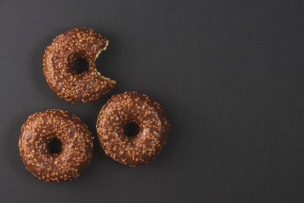 Donuts de chocolate com marca de mordida em fundo preto