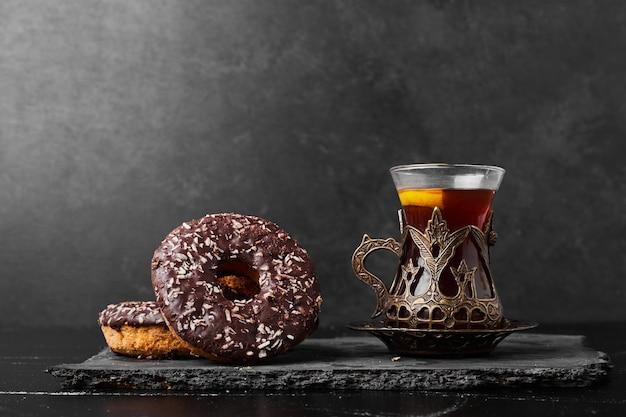 Donuts de chocolate com um copo de chá.