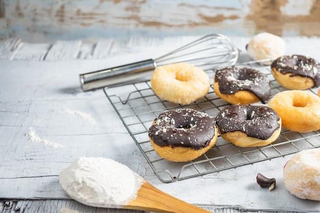 Donuts de chocolate e rosquinhas rosa na mesa da cozinha
