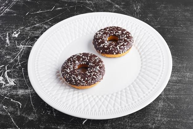 Donuts de chocolate em um prato branco.