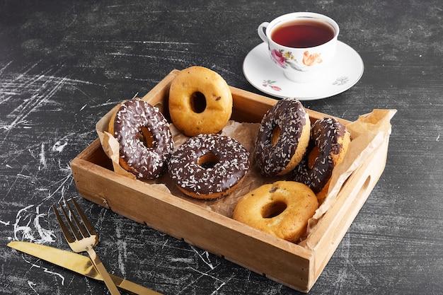 Donuts de chocolate em uma bandeja de madeira com uma xícara.