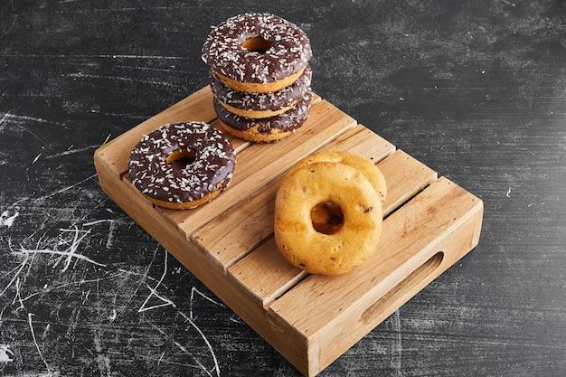 Donuts de chocolate em uma bandeja de madeira.
