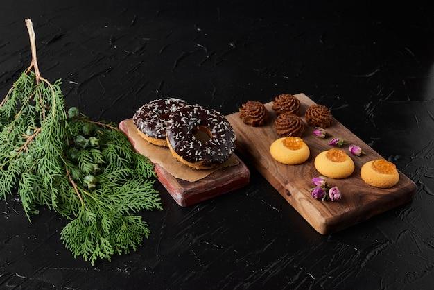 Donuts de chocolate em uma placa de madeira com bombons e biscoitos de manteiga.