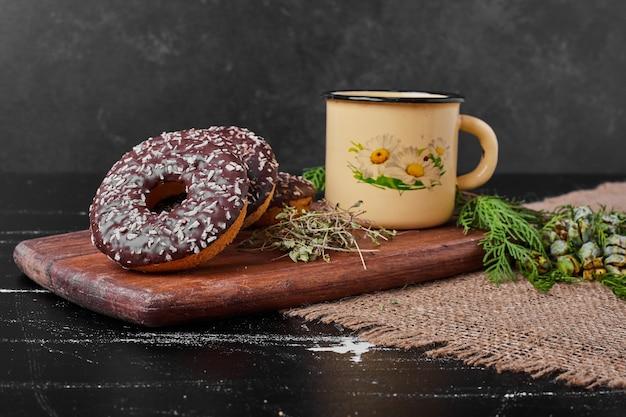 Donuts de chocolate em uma placa de madeira com chá.