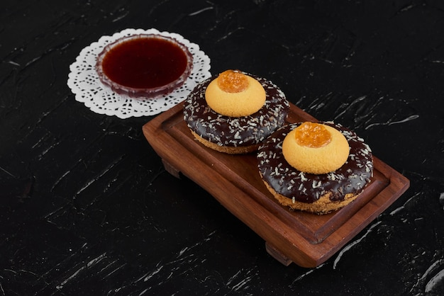 Donuts de chocolate em uma placa de madeira com confiture.