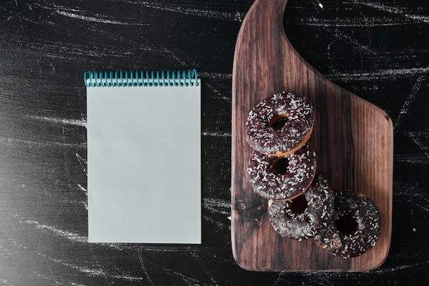 Donuts de chocolate em uma placa de madeira com livro de receitas à parte.