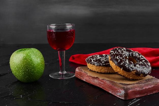 Donuts de chocolate em uma placa de madeira com maçã e vinho.